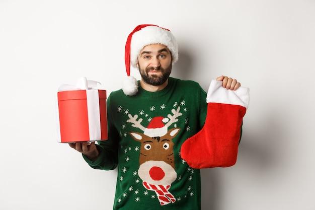 クリスマスと冬の休日のコンセプト。クリスマスの靴下とギフトボックスを持って、優柔不断に肩をすくめ、白い背景の上にサンタの帽子に立っている混乱した男。