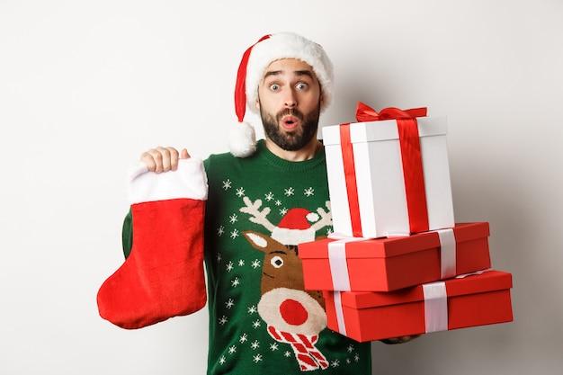 크리스마스와 겨울 휴가 개념입니다. 크리스마스 양말과 선물 상자를 들고 새해를 축하하고 나무 아래 선물을 가져오고 흰색 배경 위에 서 있는 흥분된 남자
