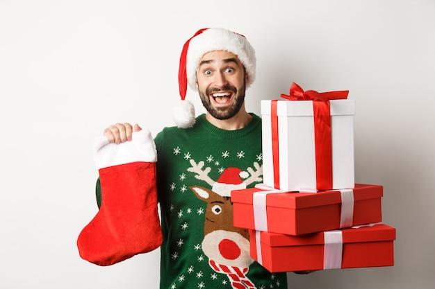 クリスマスと冬の休日のコンセプト。クリスマスの靴下とギフトボックスを持って、新年を祝って、白い背景の上に立って興奮した男