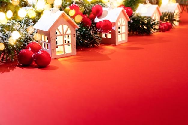 Рождественский фон. светящиеся рождественские огни белых домиков, еловые ветки, красные ягоды, огни боке, стоящие по диагонали на красном. уютная праздничная рождественская атмосфера. рождество дома концепции. скопируйте пространство.