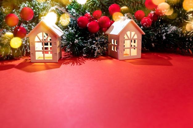 Рождественский фон. две светящиеся рождественские огни белые домики стоят с еловыми ветками, красными ягодами и золотыми огнями боке на красном. атмосфера праздника. уютное рождество дома концепции. скопируйте пространство.