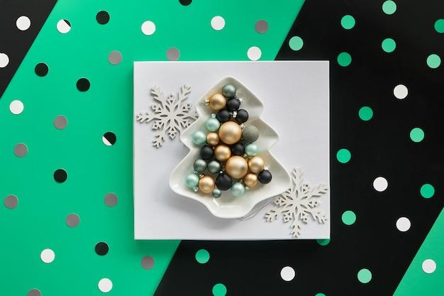Рождественские безделушки в тарелке в форме ели в белом квадрате на многослойной зеленой и черной бумаге, геометрические бумажные формы.