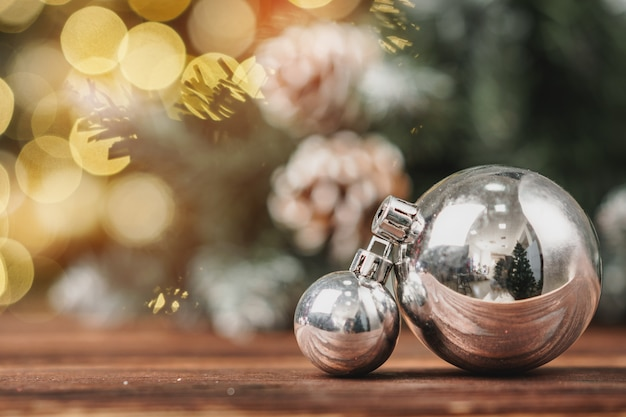 Xmas baubles on wooden table on bokeh background
