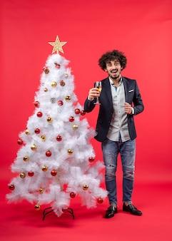 クリスマスツリーの近くに立っているワインとひげを生やした幸せな若い男とクリスマスのお祝い