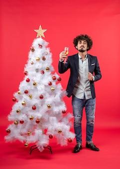 クリスマスツリーの近くに立っているワインとひげを生やした誇り高き若い男とクリスマスのお祝い