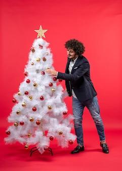 アクセサリーでクリスマスツリーを飾る幸せな面白い若い男とクリスマスのお祝い