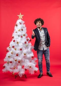 アクセサリーでクリスマスツリーの近くに立っている誰かを歓迎する幸せな面白い若い男とクリスマスのお祝い
