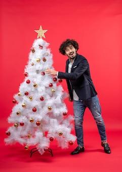アクセサリーでクリスマスツリーを飾る幸せな驚きの若い男とクリスマスのお祝い