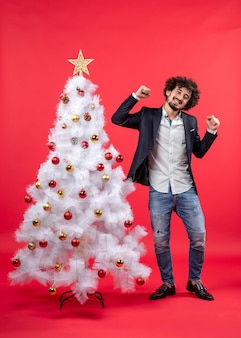 Рождественский праздник с молодым счастливым возбужденным забавным мужчиной, танцующим стоя возле елки