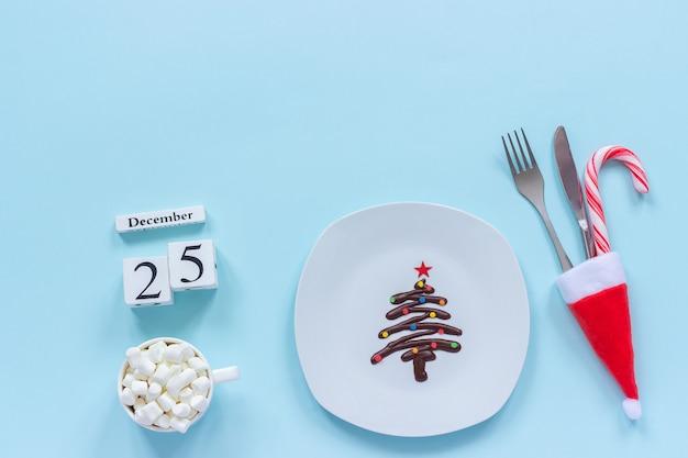 Рождественская композиция календарь 25 декабря. сладкая шоколадная елка на тарелке, столовые приборы в новогодней шапке
