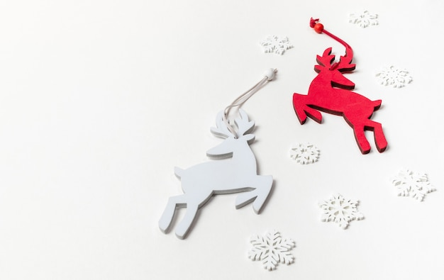 Xmas decorations two deer red and white and white wooden snowflakes on white backdrop