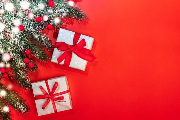Рождественский праздничный фон с еловыми ветками, покрытыми снегом, красными ягодами, двумя подарочными коробками diy, перевязанными лентами и бантами на красном.