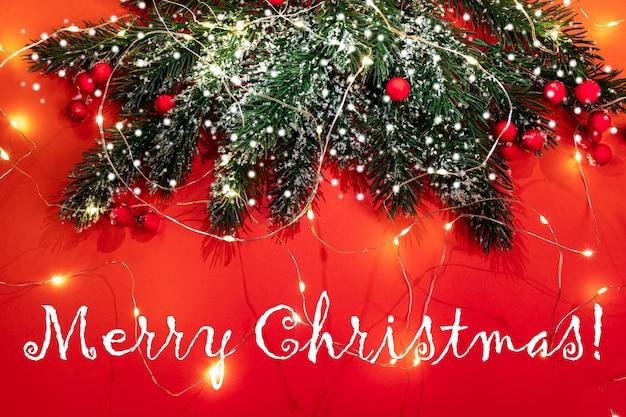 Рождественская праздничная открытка с еловыми ветками, снегом, красными ягодами, светящимися рождественскими огнями на красном фоне с надписью с рождеством. атмосфера праздника. вид сверху.