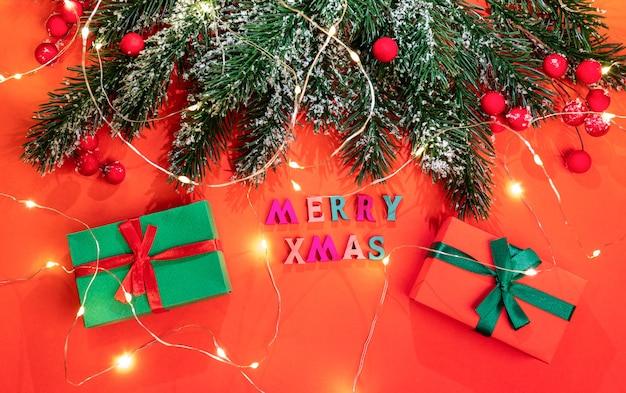 Рождественская праздничная открытка с еловыми ветками, снегом, красными ягодами, светящимися рождественскими огнями, двумя подарочными коробками diy на красном с надписью цветных деревянных букв с рождеством. атмосфера праздника. вид сверху.
