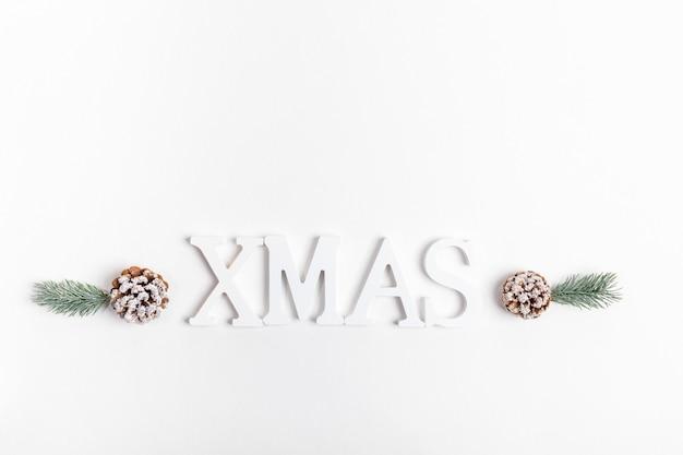 Рождественская праздничная минимальная композиция с елочными украшениями из белых букв, веток ели и сосновых шишек на белом