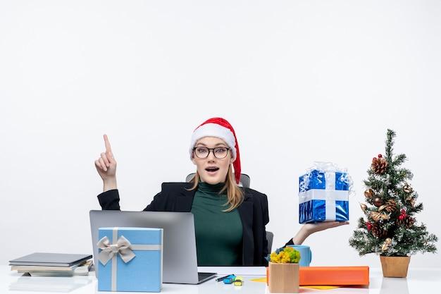 Natale - umore festivo con curioso positivo giovane donna con cappello di babbo natale e occhiali da vista seduto a un tavolo che mostra il dono rivolto sopra su sfondo bianco