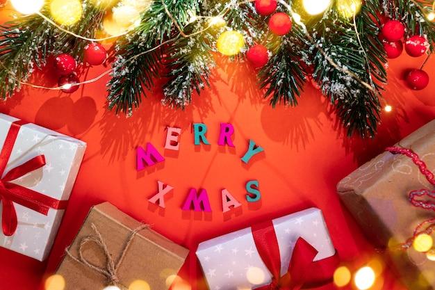 Рождественская праздничная красная открытка с еловыми ветками, светящимися рождественскими огнями, красивыми тенями, снегом, красными ягодами, цветными буквами с рождеством, набором подарочных коробок diy, золотыми огнями боке выше. вид сверху.
