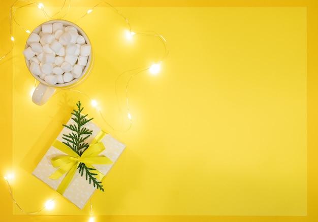 Рождественский праздничный желтый фон. чашка кофе или какао с зефиром, подарочная коробка diy и светящиеся рождественские огни на желтом. рождественский или новогодний уютный праздник. вид сверху, плоская планировка, копия пространства.