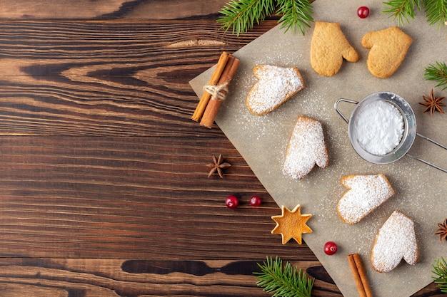 Рождественские имбирные пряники на бумаге для выпечки с сахарной пудрой на деревянном столе