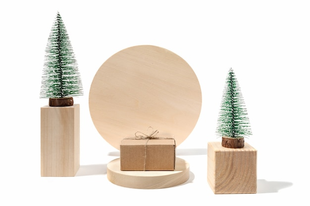 Xmas holiday composition with decorative xmas trees and diy gift cardbox on wooden podiums on white with copy space.