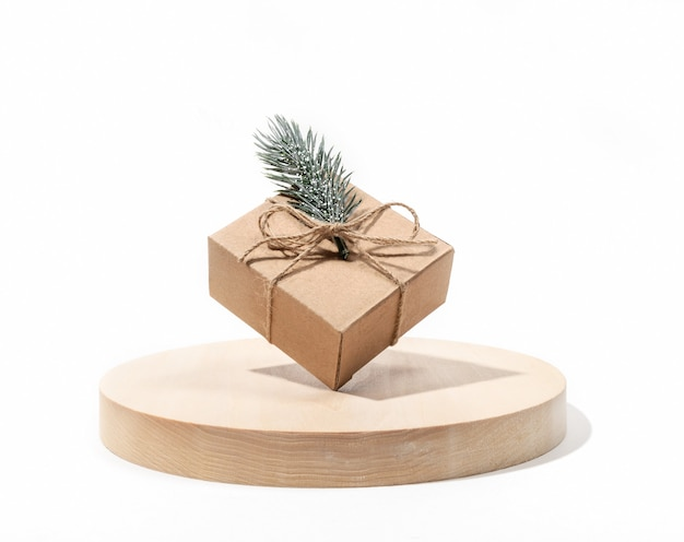 Xmas holiday composition with one diy gift cardbox balanced on round wooden stand on white background.