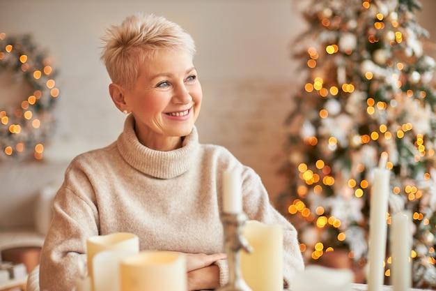 Natale, vacanze, arredamento, festa e concetto di atmosfera festosa. bella femmina di mezza età allegra con i capelli corti che gode dell'atmosfera natalizia, seduta intorno a candele di cera, decorazioni e luci