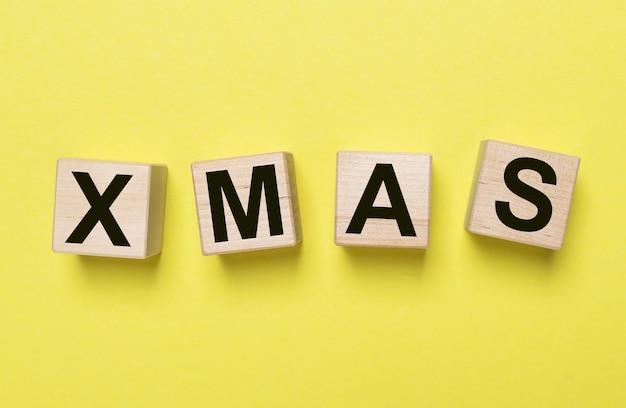 Xmas надпись на желтом минималистском фоне. счастливого рождества