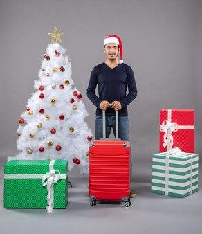 クリスマスツリーの近くに赤いスーツケースを持っているクリスマスの男