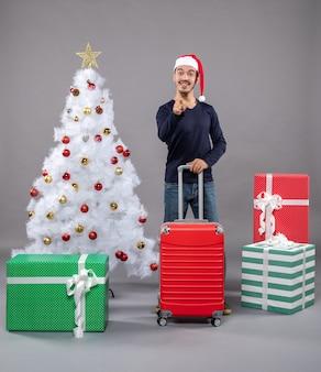 カラフルなクリスマスのおもちゃと白いクリスマスツリーの近くに赤いスーツケースを保持しているサンタの帽子を持つクリスマスの男