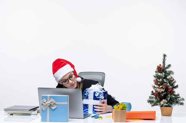 サンタクロースの帽子をかぶって、白い背景の上に贈り物とその上に新年のツリーを飾ったテーブルに座って眼鏡をかけているビジネスウーマンとクリスマス気分