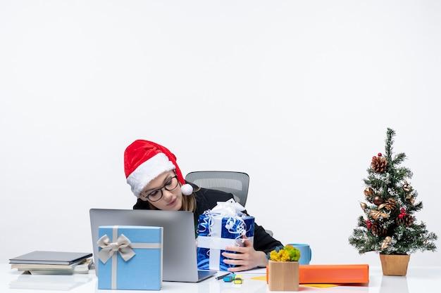 Atmosfera natalizia con donna d'affari con cappello di babbo natale e occhiali da vista seduto a un tavolo dove doni e albero di capodanno decorato su di esso su sfondo bianco