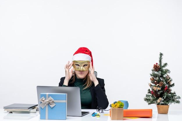 Atmosfera natalizia con donna d'affari con cappello di babbo natale e maschera da portare seduto a un tavolo su sfondo bianco