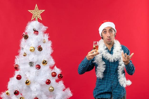 クリスマスツリーの近くでワインのグラスを上げる青いストリップシャツを着たサンタクロースの帽子をかぶった心配している若い男とクリスマスムード