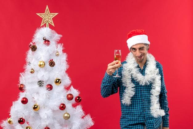 サンタクロースの帽子をかぶって、クリスマスツリーの近くでグラスワインを上げる自信を持って決心した感情的な若い男とクリスマスムード