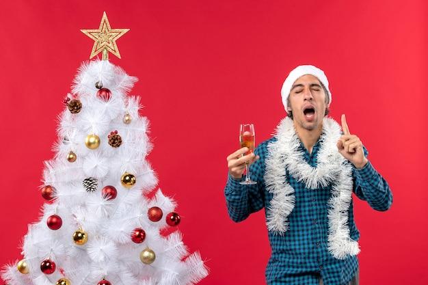 クリスマスツリーの近くでワインのグラスを上げる青いストリップシャツを着たサンタクロースの帽子をかぶった自信を持って決心した感情的な若い男とクリスマスムード