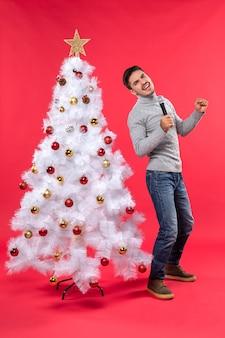 Рождественское настроение с уверенным парнем в джинсах, стоящим возле украшенной елки и держащим микрофон