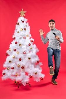 Xmas mood with confident guy dressed in jeans standing near decorated christmas tree and holding microphone greeting everyone in the party