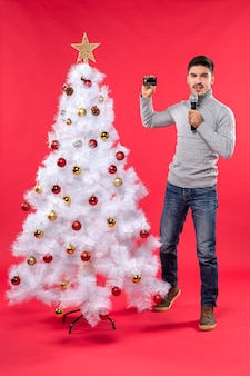 Xmas mood with confident guy dressed in jeans standing near decorated christmas tree and holding microphone and shooting a video of everyone