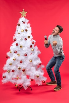Xmas mood with confident guy dressed in jeans standing near decorated christmas tree and holding microphone and singing his song
