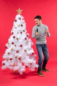 Umore natalizio con ragazzo fiducioso vestito in jeans in piedi vicino all'albero di natale decorato e tenendo il microfono cantando