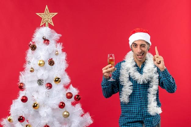 クリスマスツリーの近くでワインのグラスを上げる青いストリップシャツでサンタクロースの帽子をかぶった自信を持って幸せな狂気の感情的な若い男とクリスマスムード