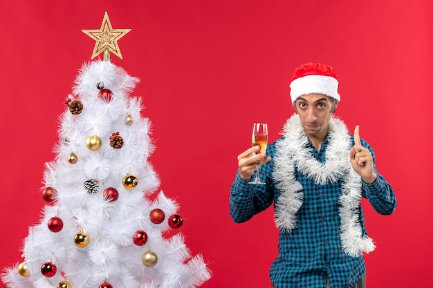 クリスマスツリーの近くでワインのグラスを上げる青い縞模様のシャツを着たサンタクロースの帽子をかぶった決意の若い男とクリスマスムード
