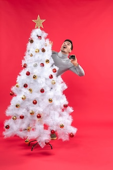 Xmas mood with emotional guy standing behind the decorated christmas tree and looking above