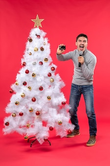 Xmas mood with emotional guy standing near decorated christmas tree and holding microphone and phone singing his song