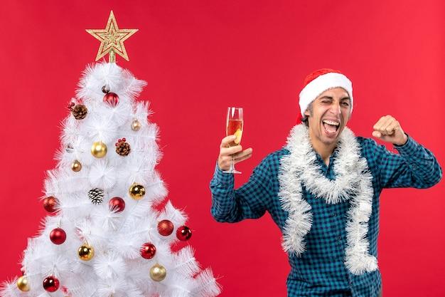 Umore di natale con emotivo giovane pazzo orgoglioso con il cappello di babbo natale in una camicia blu spogliata che tiene un bicchiere di vino vicino all'albero di natale
