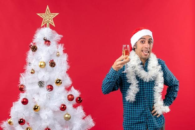 산타 클로스 모자와 와인 한 잔을 올리는 감정적 인 젊은이와 크리스마스 분위기가 크리스마스 트리 근처에서 자신을 응원합니다.