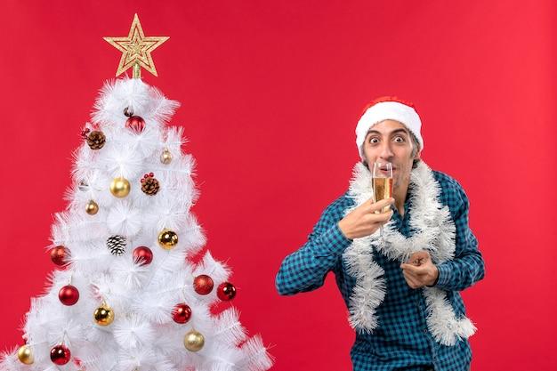 クリスマスツリーの近くでグラスワインを飲む青い縞模様のシャツを着たサンタクロースの帽子をかぶった感情的な若い男とクリスマスムード