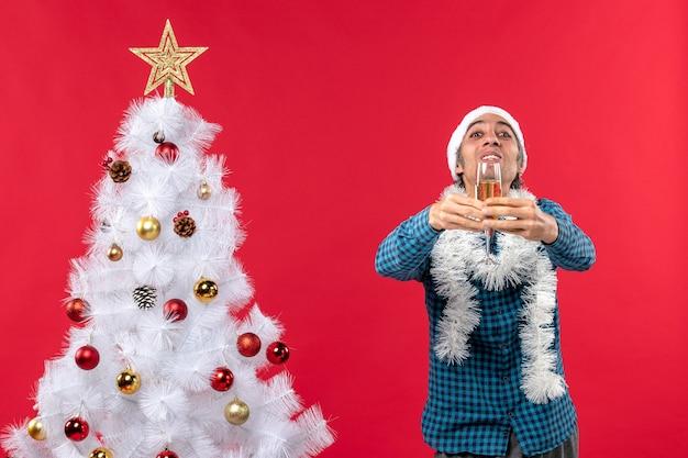 クリスマスツリーの近くの誰かにワインのグラスを与える青い縞模様のシャツにサンタクロースの帽子をかぶった感情的な若い男とクリスマスムード