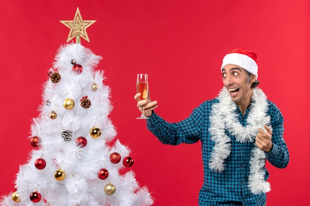 Рождественское настроение с эмоциональным молодым человеком в шляпе санта-клауса в синей полосатой рубашке, держащим бокал вина, позирующим возле елки
