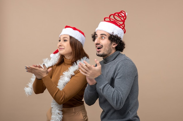 Xmas mood with excited cool satisfied lovely couple wearing red santa claus hats applauding someone